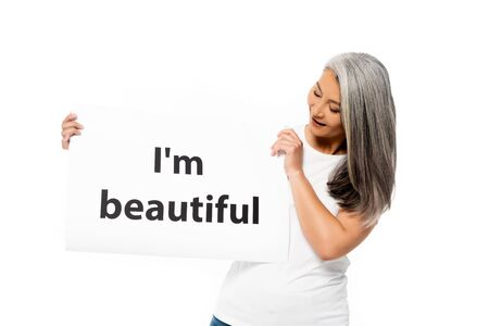 happy asian woman holding placard with i`m beautiful lettering isolated on white