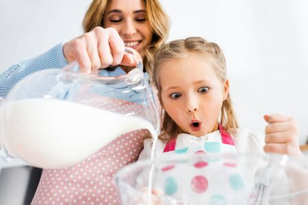 Low angle view of shocked daughter looking at mother pouring milk from jug in bowl