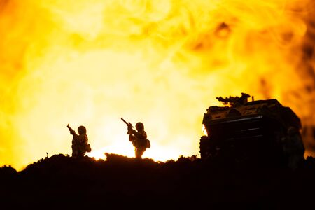 Battle scene with silhouettes of toy tank and soldiers with fire at background Stock fotó