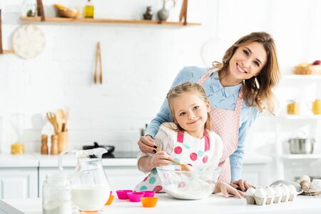 Selective focus of mother and daughter smiling and cooking delicious cupcakes with ingredients like eggs, milk and flour