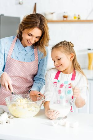 smiling mother cooking with balloon whisk and daughter holding jug with milk Reklamní fotografie