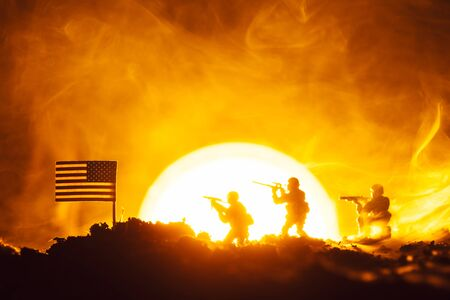 Battle scene of toy soldiers, american flag and fire with sunset at background Stock fotó