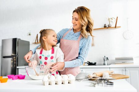 Beautiful attractive mom and cute daughter looking at each other and cooking delicious cupcakes together