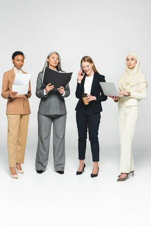 multicultural businesswomen with folders near woman talking on smartphone on white Stock Photo