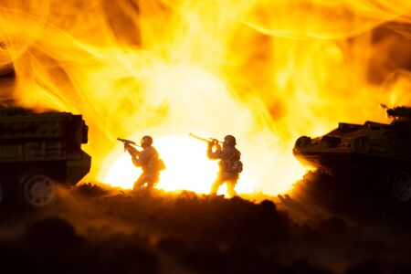 Silhouettes of toy warriors with tanks in fire and sunset at background, battle scene Stock fotó