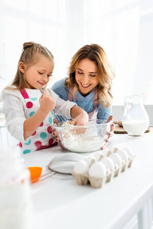 Selective focus of mother looking at daughter kneading dough in bowl at jug of milk, eggs, flour and cooking utensils