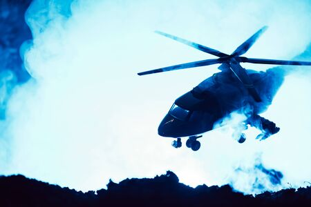 Battle scene with toy helicopter above battleground with smoke on blue background