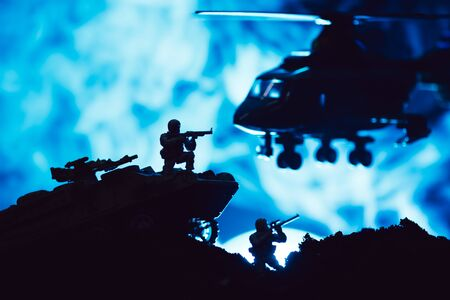 Scene of battle with toy warriors, tank and helicopter with smoke on blue background Stock fotó