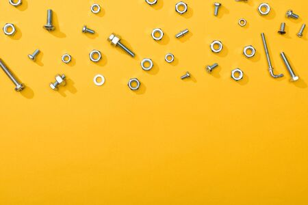 Top view of metal nuts and bolts on yellow background with copy space 写真素材