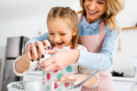 Selective focus of attractive mother and cute daughter laughing during adding  ingredients to dough in bowl