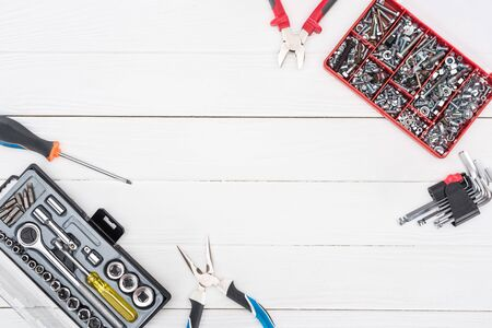 Top view of tool boxes with pliers, hex keys and wrench on white wooden background 写真素材
