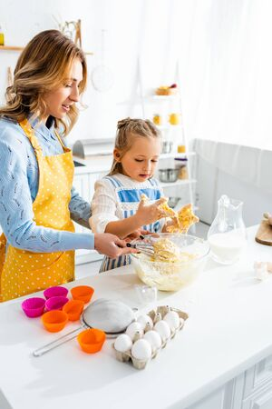 mother and daughter in aprons mixing dough in kitchen