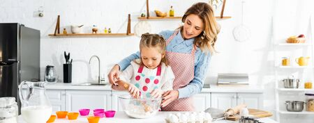 Beautiful attractive mother standing behind cute daughter while kneading dough, panoramic shot Reklamní fotografie