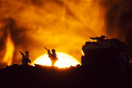 Silhouettes of toy warriors and tank on battleground with sunset and fire at background