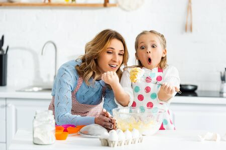 Mother and shocked, excited child looking at balloon whisk in dough above bowl Reklamní fotografie