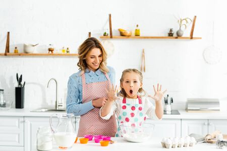 Cute daughter with open mouth holding up hands standing with mom at table Reklamní fotografie