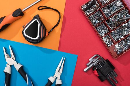 Top view of tool set with pliers and measuring tape on colorful background