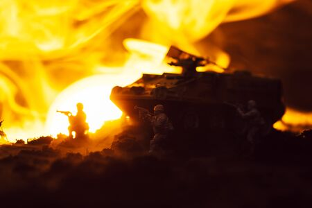 Toy soldiers with tank, fire and sunset on black background, battle scene Stock fotó