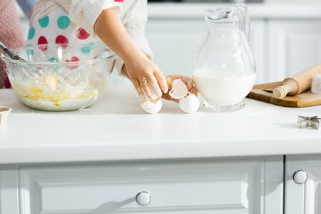 Cropped view of child breaking eggs into bowl in kitchen