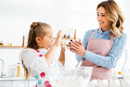 Selective focus of smiling mom and daughter with open mouth holding up hands having fun during kneading dough