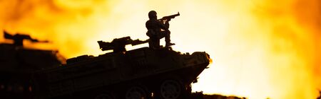Battle scene with silhouette of toy soldier on tank with fire at background, panoramic shot Stock fotó