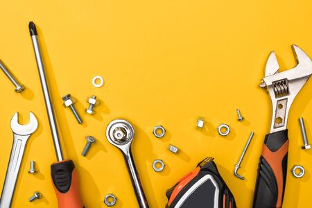 Top view of tool set with nuts and bolts on yellow background