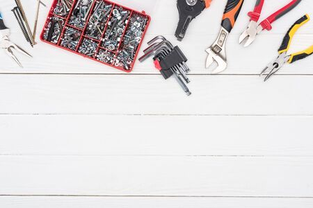 Top view of tool box with pliers and wrench on white wooden background 写真素材