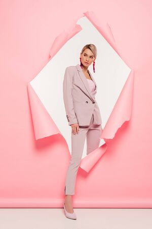 attractive stylish girl in suit posing in torn paper, on white