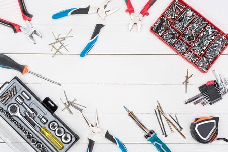Frame of tools with tool boxes on white wooden surface
