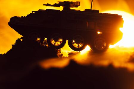Battle scene with toy tank in fire and sunset at background Stock fotó