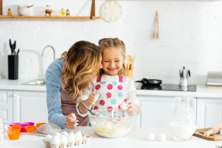 Mother and daughter smiling and happy during making dough for cupcakes together Reklamní fotografie - 139884556