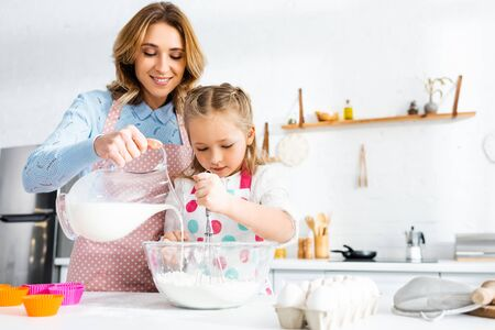 Daughter kneading dough while mother pouring milk from jug in bowl in kitchen Reklamní fotografie