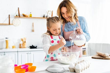Selective focus of daughter kneading dough while mother pouring milk from jug in bowl at home
