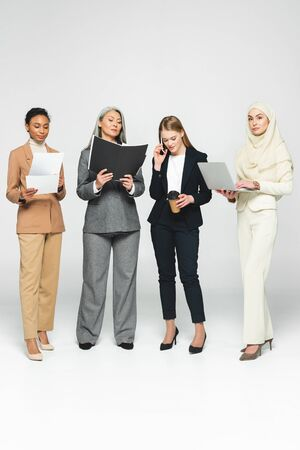 attractive multicultural businesswomen with folders near woman talking on smartphone on white