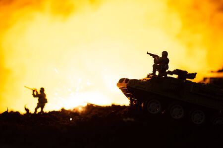 Toy soldiers, tanks and explosion on battleground with fire at background