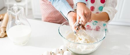 Cropped view of mother and daughter kneading dough together in bowl