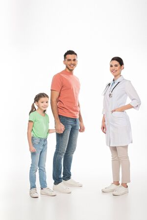 Full length of pediatrician near father with daughter smiling at camera on white background