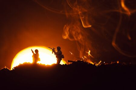 Battle scene with toy soldiers on battleground with smoke and sunset at background