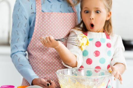 Selective focus of shocked and excited child looking at balloon whisk in dough above bowl Reklamní fotografie