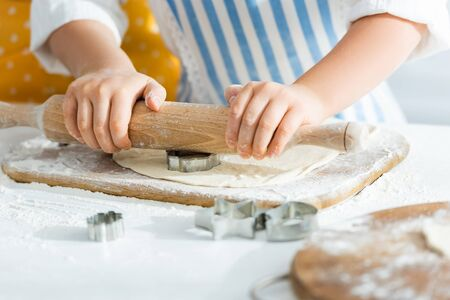 cropped view of kid rolling dough with rolling pin