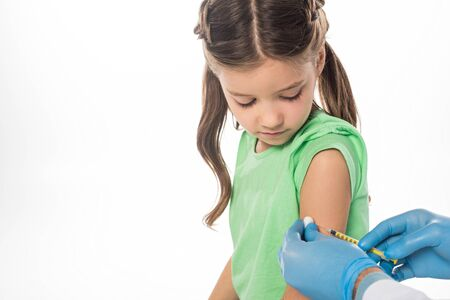 Side view of kid looking at pediatrician doing vaccine injection isolated on white