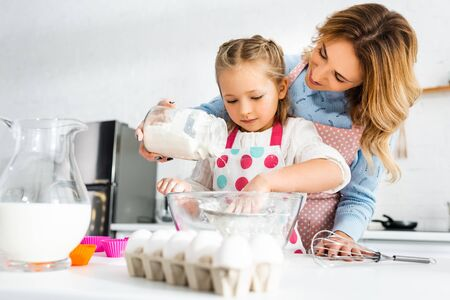 Mother and daughter sifting dough for cupcakes through sieve Reklamní fotografie