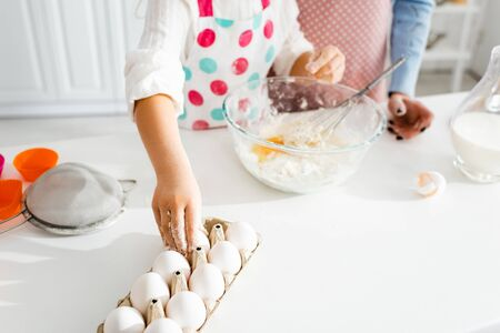 Selective focus of child hand taking egg for dough in kitchen Reklamní fotografie - 139824239