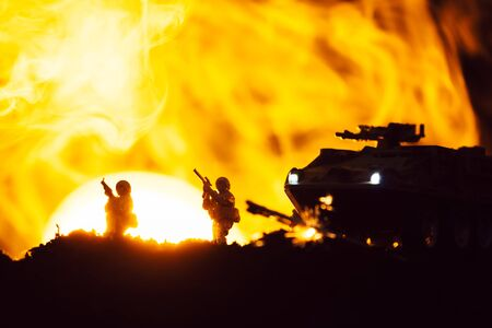 Scene of battle with toy warriors, tank and smoke with sunset at background