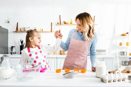smiling mother holding hands with cute daughter in kitchen Reklamní fotografie - 139883308