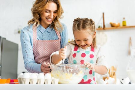 Beautiful attractive mother and cute daughter happy and positive cooking cupcakes together at home Reklamní fotografie