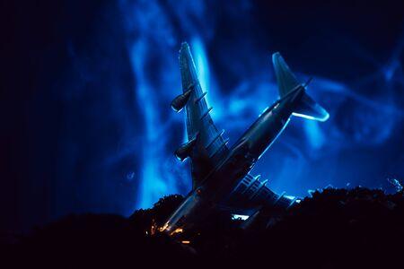 Battle scene with crash of toy plane with blue smoke on black background Stock fotó