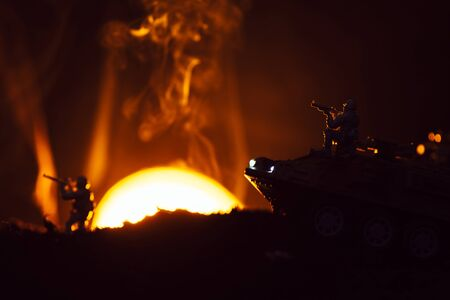 Battle scene with toy warriors and tank in smoke with sunset at background