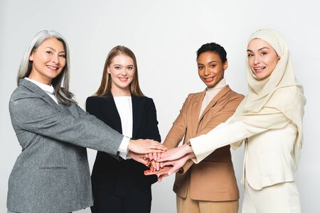 multicultural businesswomen putting hands together isolated on white