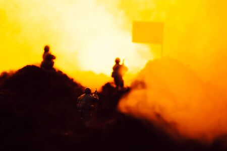 Selective focus of toy warriors on battleground with smoke, flag and fire at background Stock fotó